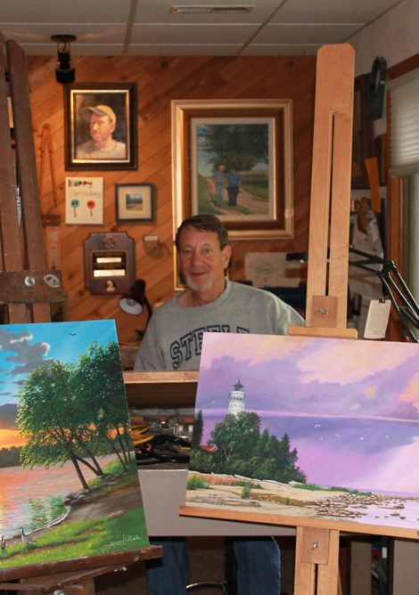 Gregory D. Steele in his workshop, displaying two of his paintings